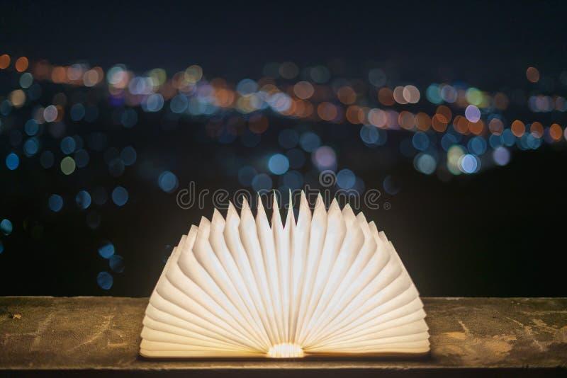 Un libro que se abre con la luz en un papel como magia, colocado en un piso del cemento con un fondo del bokeh para la Navidad En fotos de archivo