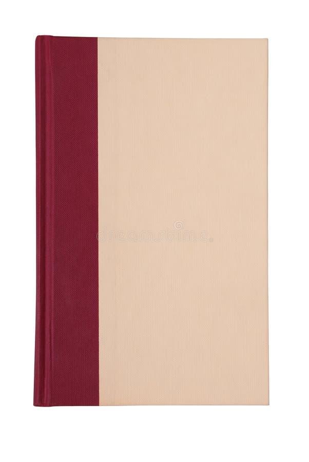 Un libro se aísla en el blanco, cubierta tiene colores del beige y del clarete, imagen de archivo