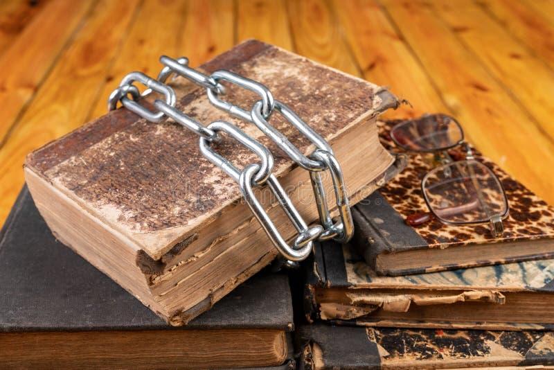Un libro viejo limitado por una cadena brillante del metal La literatura prohibida arregló en una tabla de madera foto de archivo