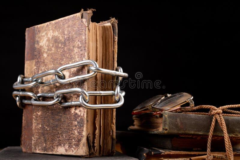 Un libro viejo limitado por una cadena brillante del metal La literatura prohibida arregló en una tabla de madera imagen de archivo libre de regalías