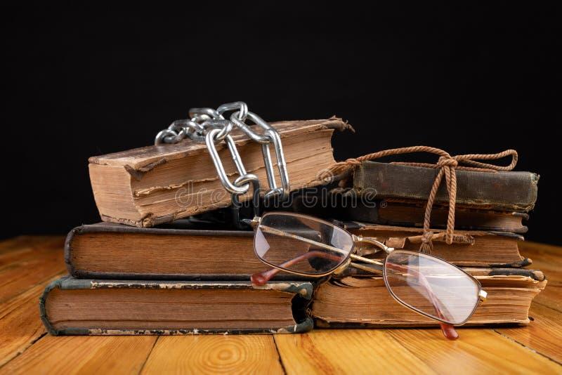Un libro viejo limitado por una cadena brillante del metal La literatura prohibida arregló en una tabla de madera fotos de archivo