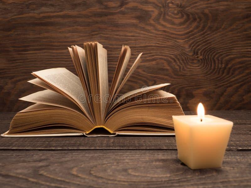Un libro viejo y una vela en una tabla de madera fotos de archivo