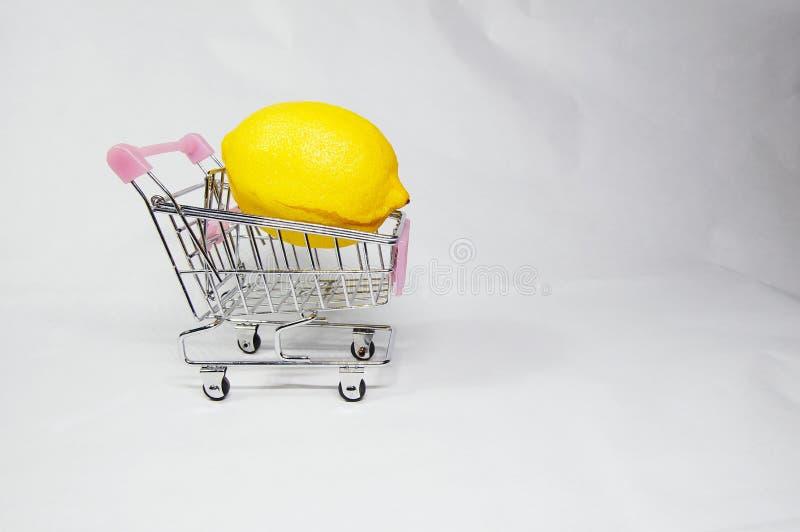 Un limone on/inside il mini carrello di compera fotografia stock