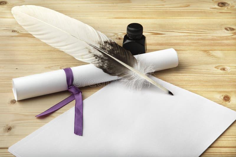 Un limpio del papel en blanco, de una voluta, de una pluma del ganso, y de una botella de tinta negra está situado en una tabla d fotos de archivo libres de regalías