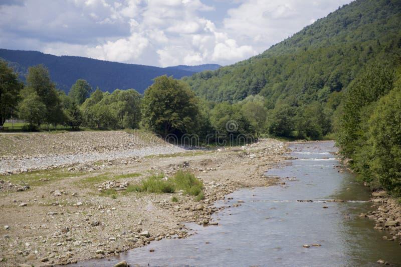 Un lit de la rivière d'une rivière de montagne entourée par les montagnes boisées dessus image libre de droits