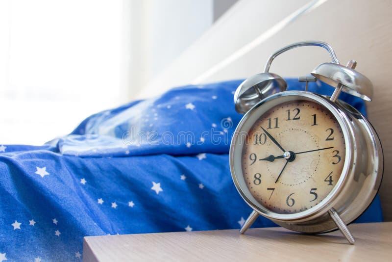 Un lit vide avec un réveil photographie stock