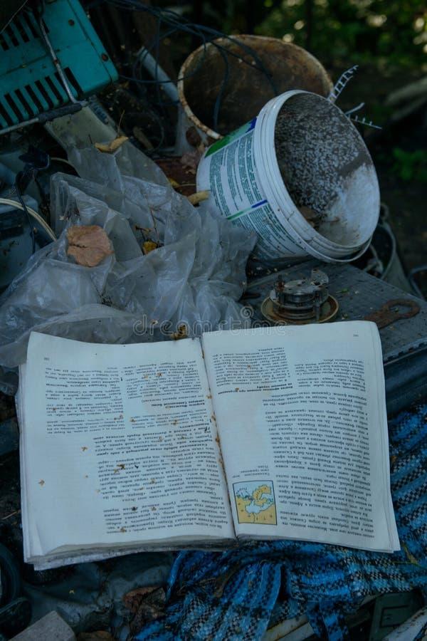 Un livre abandonné avec des ordures dans une décharge image libre de droits