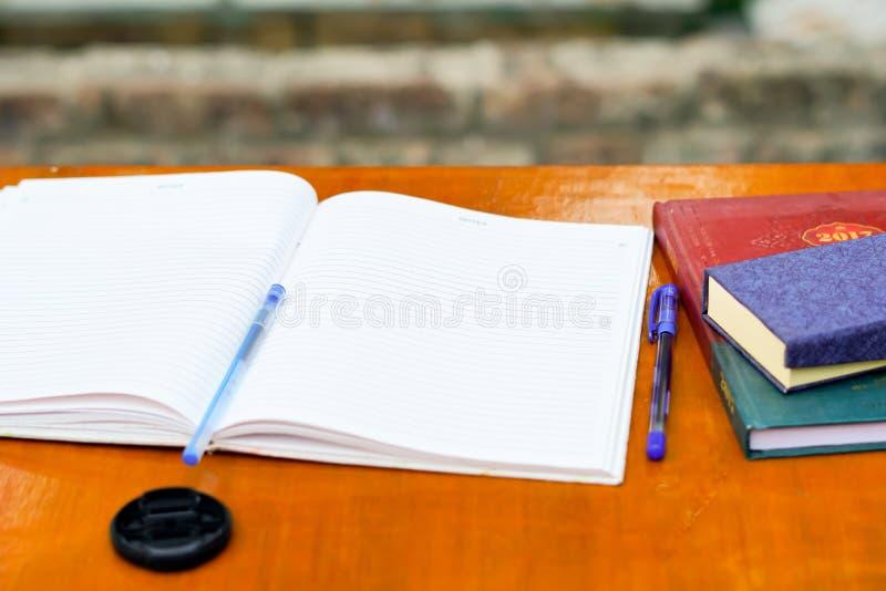 Un livre d'exercice ouvert sur une table noir image stock