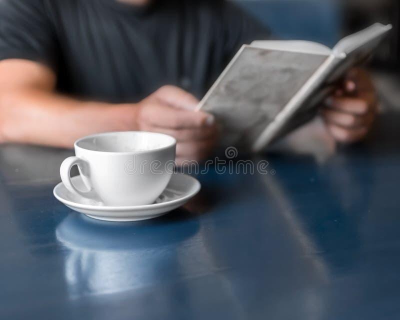 Un livre de lecture d'homme et un café potable se reposant en café ou à la maison dans la cuisine au temps de matin Une tasse de  image stock