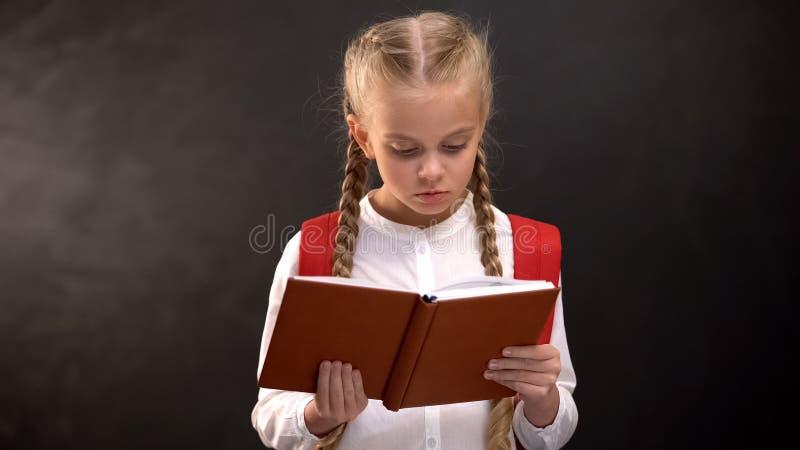 Un livre de lecture pour les filles intelligentes, un tableau sur fond, la soif de connaissances photos libres de droits