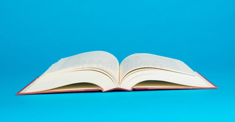 Un livre ouvert sur un fond bleu photos libres de droits
