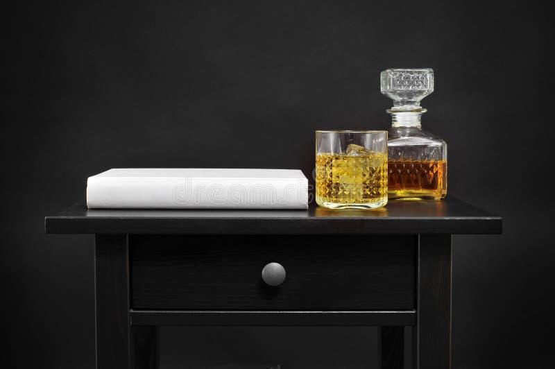 Un livre, une bouteille et un verre avec la boisson alcoolisée sur une table, au-dessus d'un blac image libre de droits