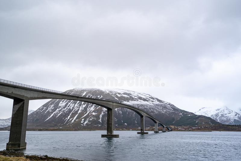 Un long pont concret pour des voitures et des camions traversant la mer sous le ciel nuageux photo stock