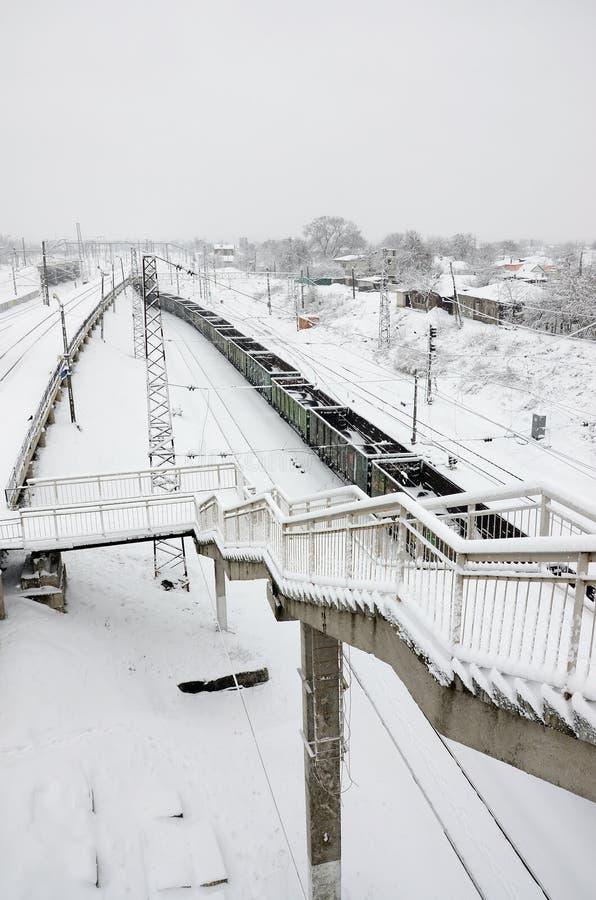 Un long train des voitures de fret se déplace le long de la voie ferrée Paysage ferroviaire en hiver après des chutes de neige image stock