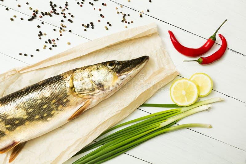 Un luccio fresco con le spezie su un fondo di legno bianco Cucina europea, pesce del fiume immagini stock