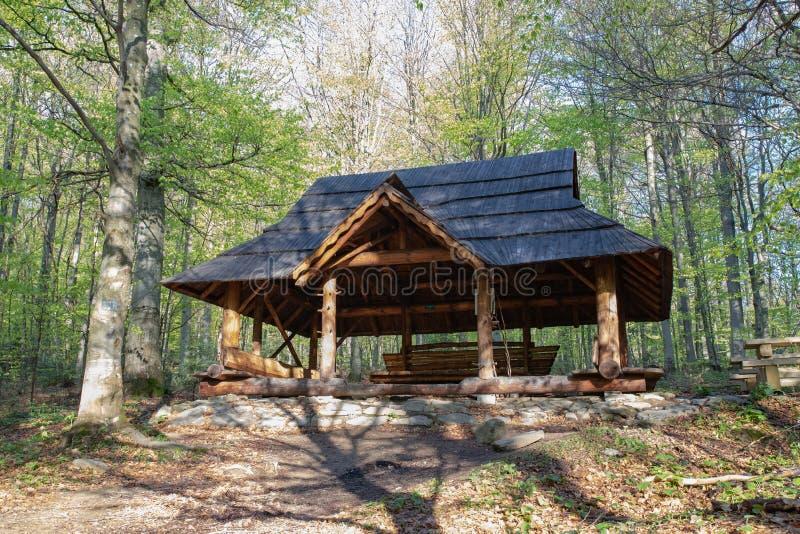 Un lugar del refugio para los turistas en el rastro en las montañas Refugio de madera bajo la lluvia imagenes de archivo
