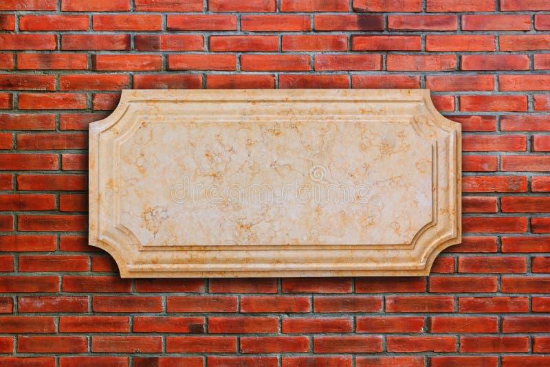 Un mármol del letrero en la pared de ladrillo imágenes de archivo libres de regalías
