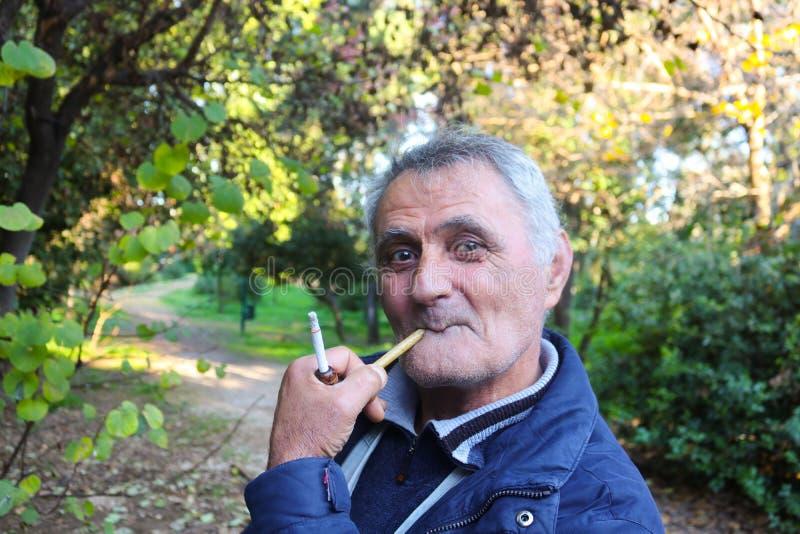 Un más viejo hombre armenio que fuma un tubo en el parque Atenas Grecia 1-3-2018 fotos de archivo