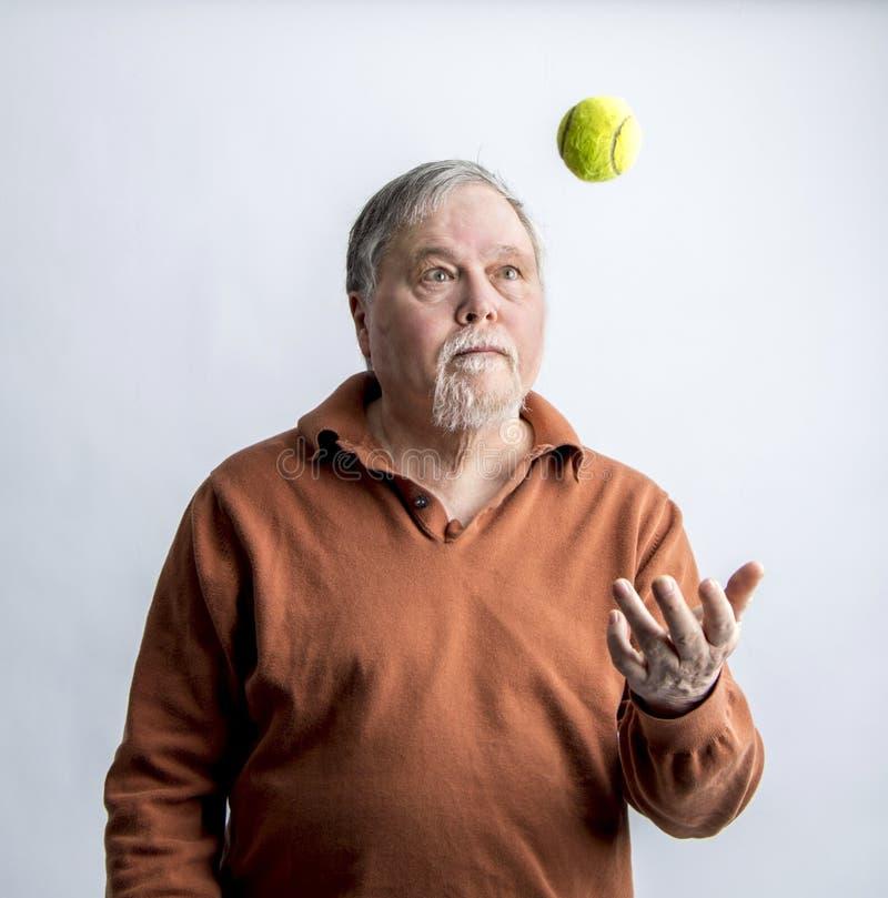 Un más viejo hombre barbudo en suéter anaranjado que lanza la pelota de tenis verde imágenes de archivo libres de regalías