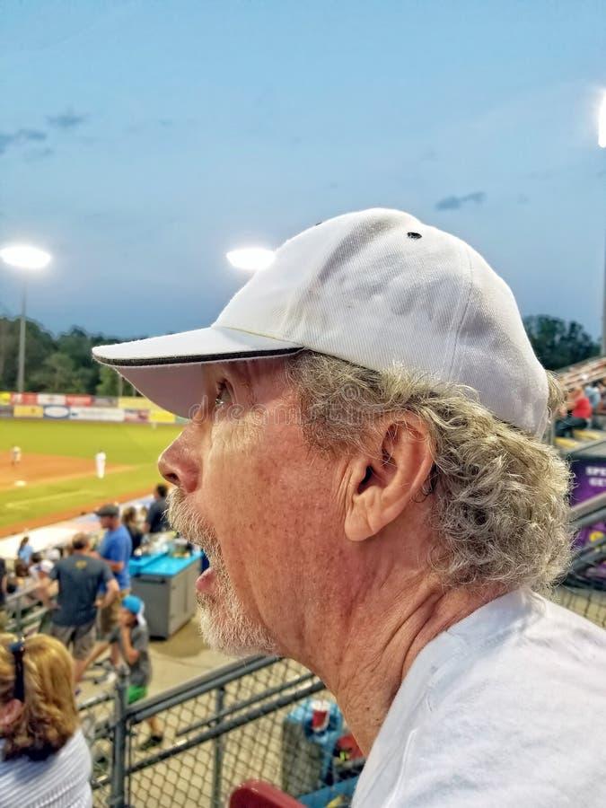 Un más viejo hombre con la perilla y el sombrero blanco que miran para arriba el cielo un b foto de archivo