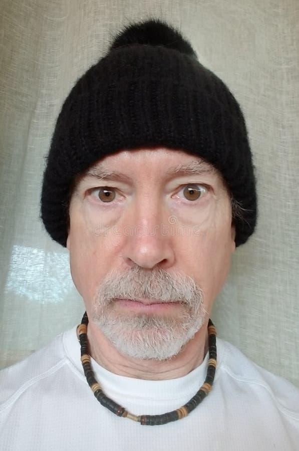 Un más viejo hombre en negro wollen el casquillo imagen de archivo libre de regalías