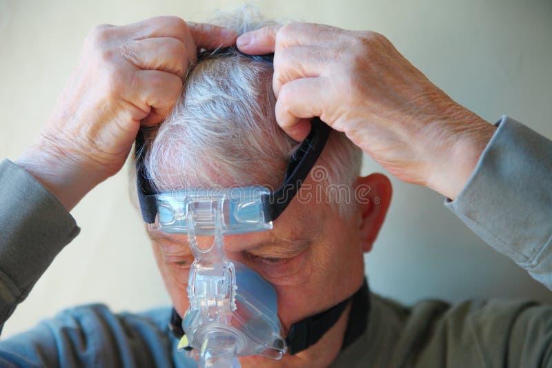 Un más viejo hombre pone el engranaje principal del dispositivo de CPAP fotos de archivo libres de regalías