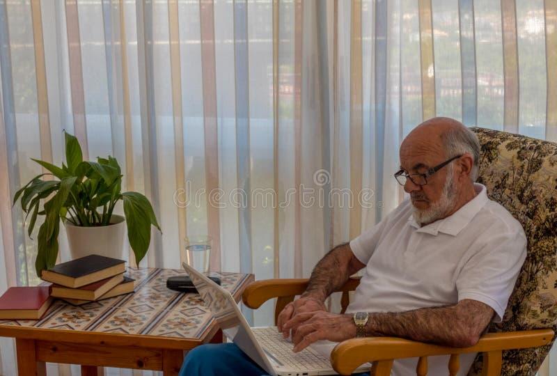 Un más viejo hombre que se sienta en la silla con el ordenador portátil foto de archivo