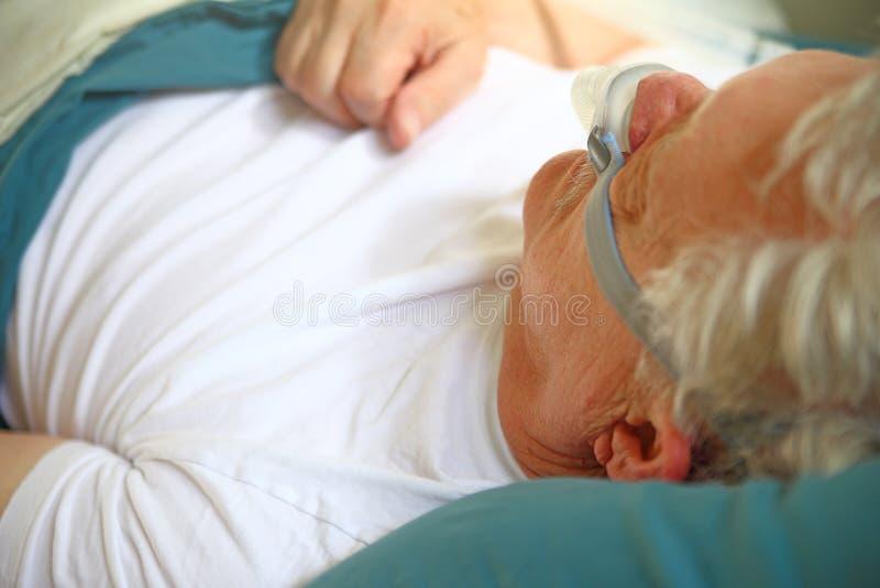 Un más viejo hombre que usa el dispositivo del apnea de sueño foto de archivo