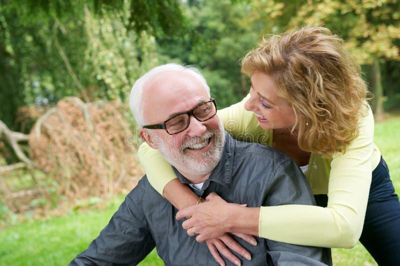 Un más viejo hombre y mujer que sonríen al aire libre imagen de archivo