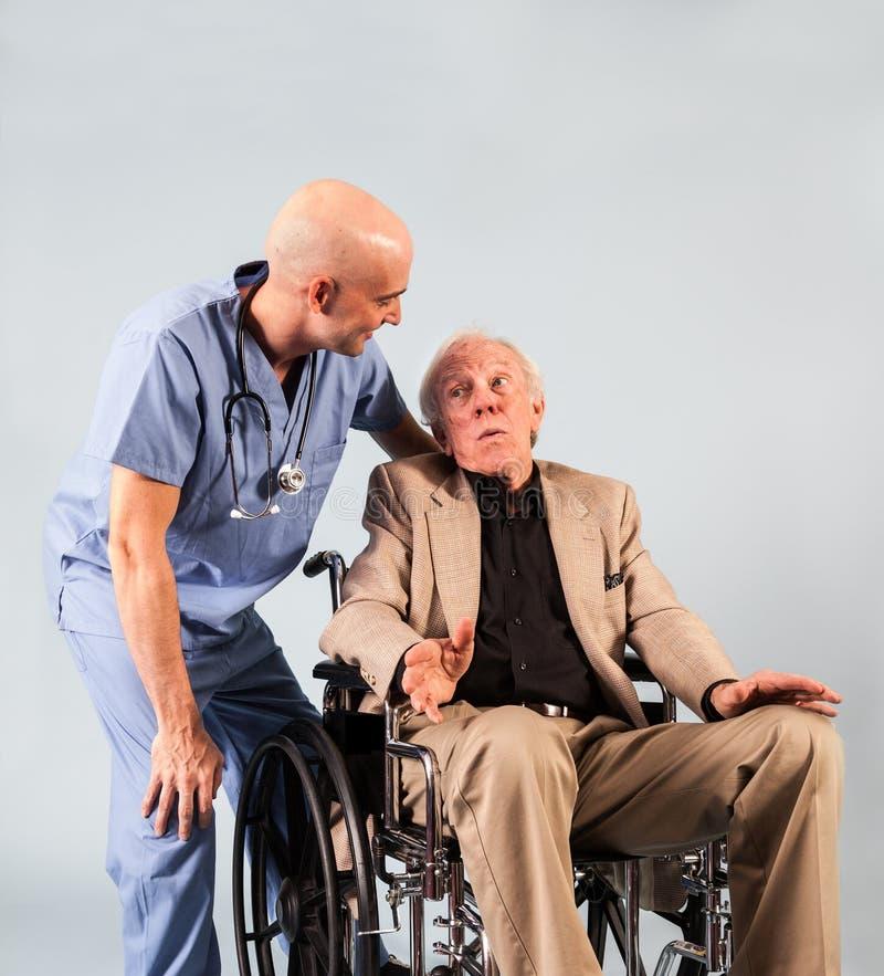 Un más viejo paciente habla con la enfermera de sexo masculino imagenes de archivo