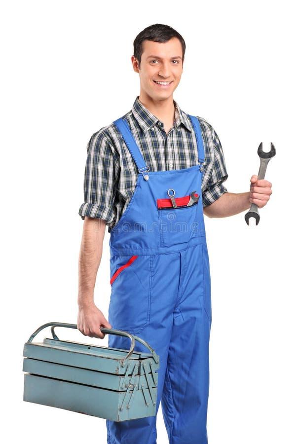 Un mécanicien dans le verall retenant une boîte à outils images stock