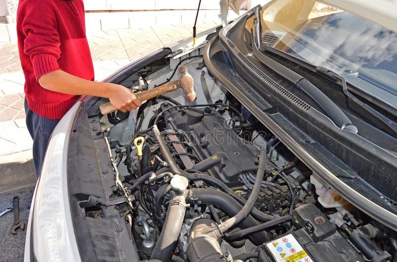 Un mécanicien de voiture Using un marteau photographie stock libre de droits