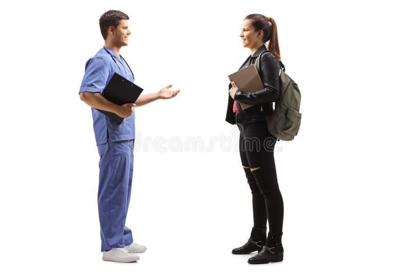 Un médecin en uniforme bleu parlant à une jeune patiente photo stock