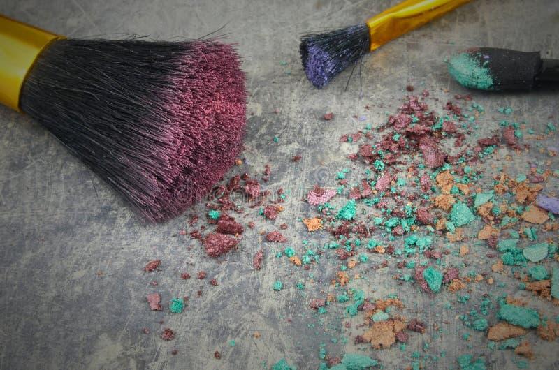Un mélange des fards à paupières et des applicateurs s'est émietté sur une table en acier rustique Pêle-mêle déroutant des produi photo stock