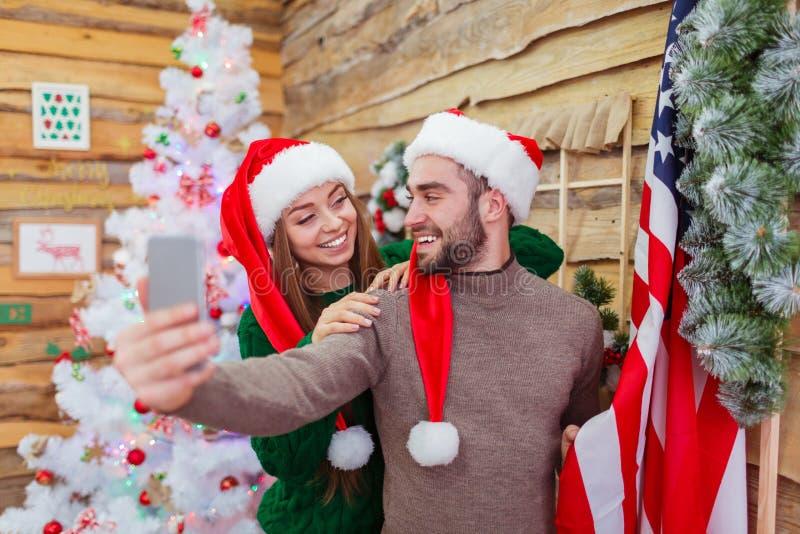 Un ménage marié fait le selfie sur le fond d'un arbre de Noël photographie stock libre de droits