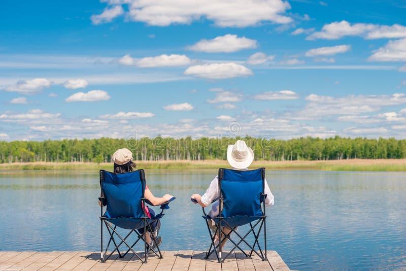 Un ménage marié se reposant sur des chaises près d'un lac pittoresque images libres de droits