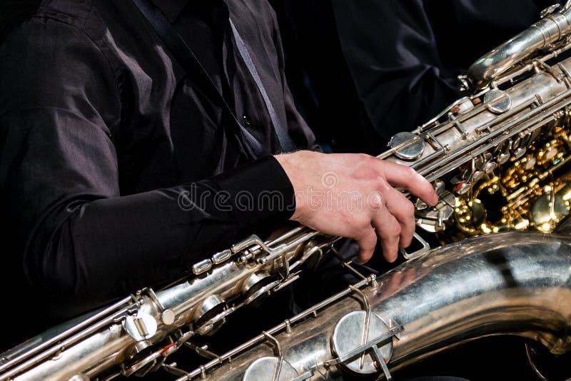 Un músico en ropa negra sienta y sostiene un saxofón del barítono con su mano derecha Para la información sobre el tema musical fotos de archivo