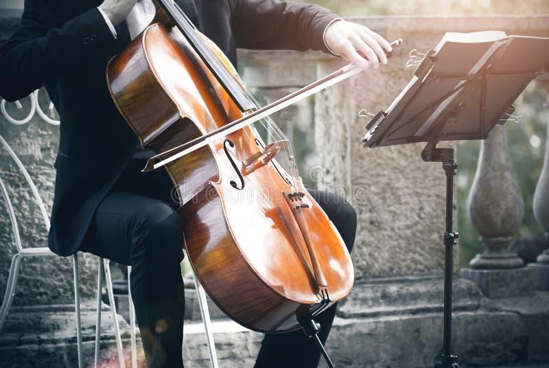 Un músico juega el violoncelo con un arco y la mirada de la notación musical imagenes de archivo