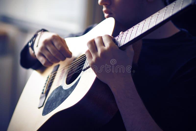 Un músico toca su guitarra acústica, sosteniendo el fretboard en la base fotografía de archivo libre de regalías