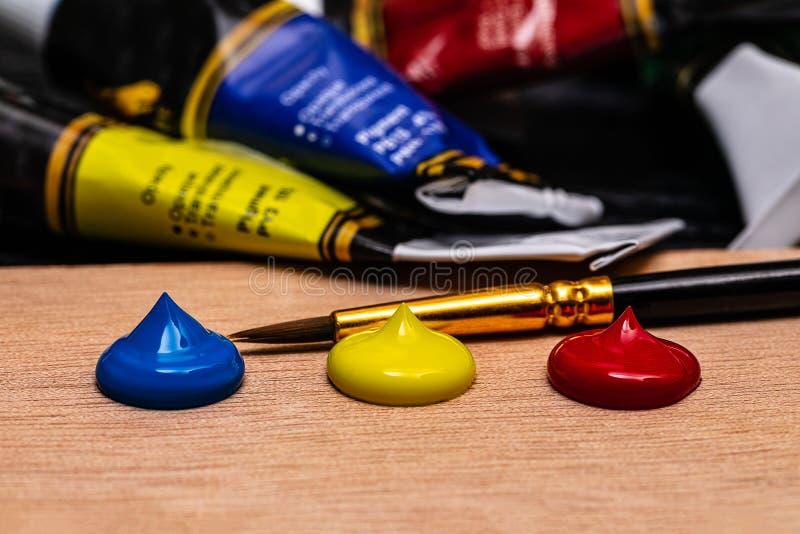 Un macro de 3 limandes des peintures acryliques de l'artiste dans les couleurs primaires rouges, jaunes et bleues avec les baquet images stock