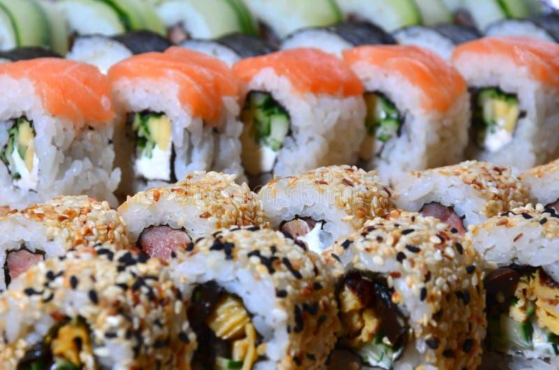 Un macro tir d'un ensemble de sushi de beaucoup roule est situé sur une planche à découper en bois sur une table dans la cuisine  photographie stock
