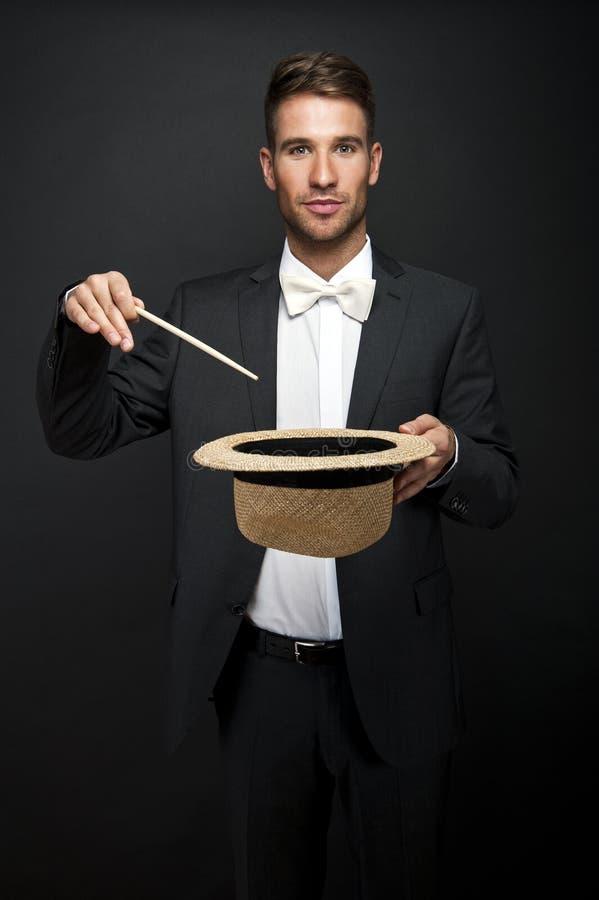 Un magicien dans un costume noir tenant un chapeau supérieur vide photo libre de droits