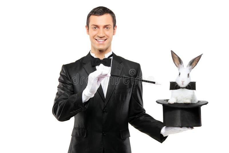 Un mago che tiene un cappello superiore con un coniglio in esso fotografie stock