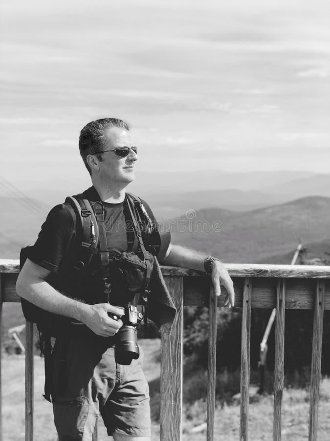 Un maigre d'homme contre une balustrade avec le fond d'arête de montagne photo libre de droits