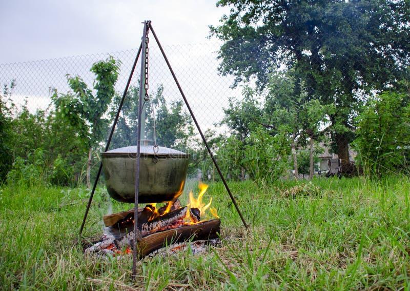 Un man' la mano di s accende un fuoco sotto una pentola, che sta su un fuoco fotografia stock libera da diritti