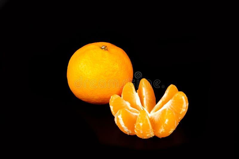 Un mandarino fresco ed un sbucciati sul nero fotografie stock