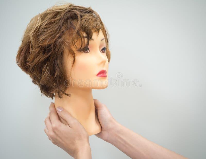 Un manichino si dirige verso il lavoro di parrucchiere d'istruzione in mani su un fondo leggero Concetto di bellezza fotografie stock libere da diritti