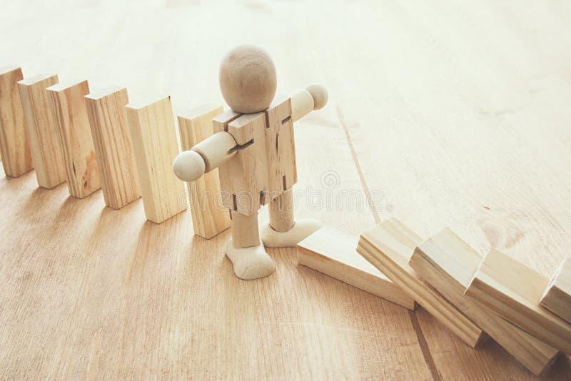 Un maniquí de madera que para el efecto de dominó ejecutivo retro de la imagen del estilo y concepto de control del riesgo imágenes de archivo libres de regalías