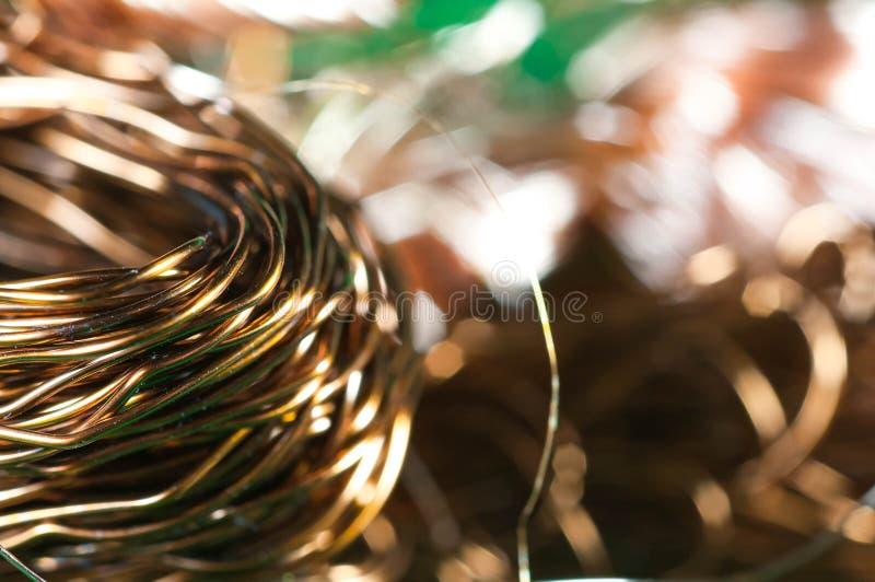 Un manojo de alambres de cobre en una caja verde para reciclar foto de archivo