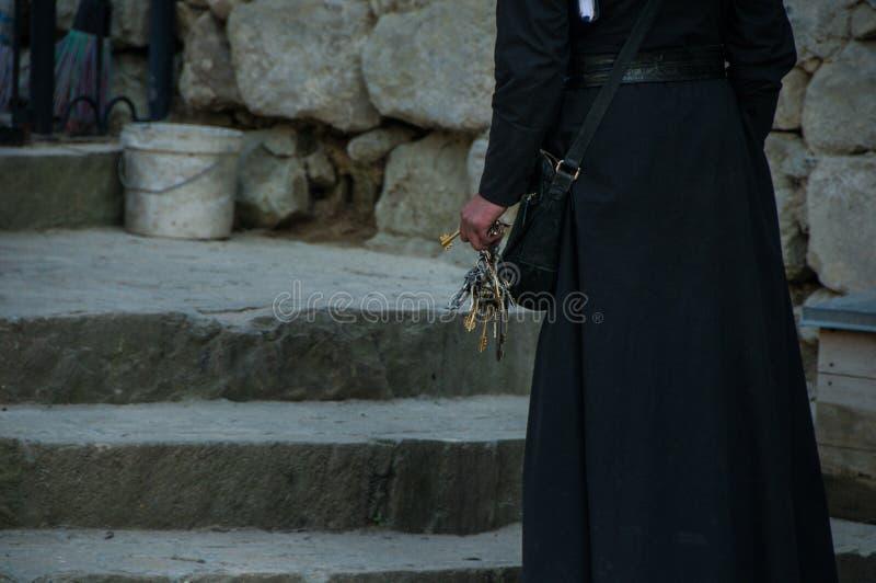 Un manojo de llaves en la mano del sacerdote imagen de archivo libre de regalías